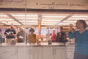 teacher teaching students with equations on a window in a lab