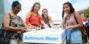 people drinking from a water fountain that says baltimore water